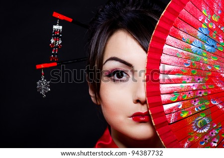Beautiful young woman in Asian costume with red Asian fan on  background.