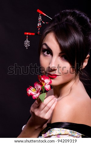 Beautiful young woman in Asian costume with red flowers on black background.