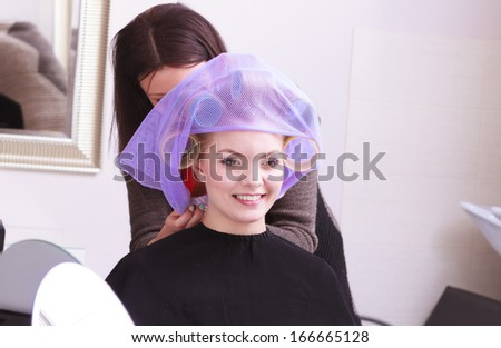 Beautiful young woman in beauty salon. Blond girl with hair curlers rollers by hairdresser. Hairstyle.