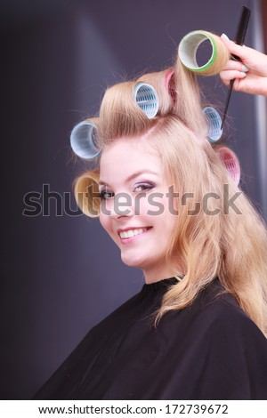 Beautiful young woman in beauty salon. Blond smiling girl with hair curlers rollers by hairdresser. Hairstyle.