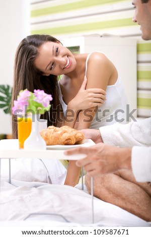 beautiful young woman in bed looking in her husband serving breakfast, thanks for breakfast
