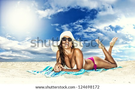 Beautiful young woman in bikini laying on the beach