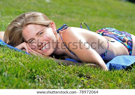 Beautiful young woman in bikini laying out in the sunshine - tanning - on a blue blanket and smiling