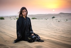 Beautiful young woman in black dress sitting in the desert.