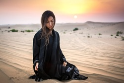 Beautiful young woman in black dress sitting on sand in the desert.