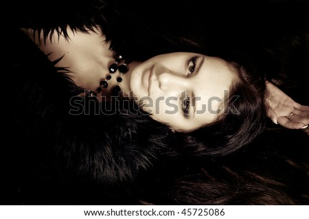 beautiful young woman in black fur with black necklace
