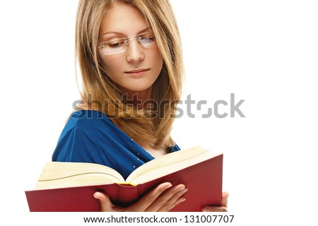 Beautiful young woman in blue dress and glasses reads red book, isolated on white background.