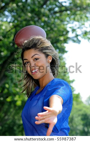 Beautiful young woman in blue mesh football jersey with ball - throwing
