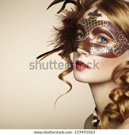 Beautiful young woman in brown mysterious venetian mask. Fashion photo