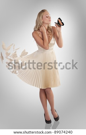 beautiful young woman in butterfly dress holding a and kissing the same insect