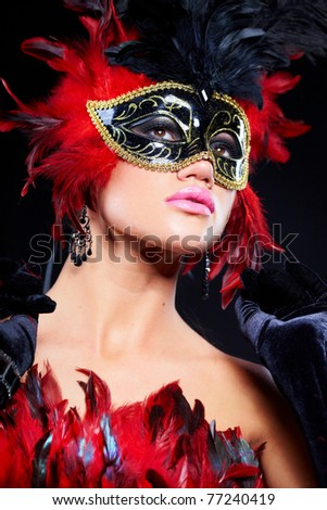 Beautiful young woman in carnival mask and feather boa.