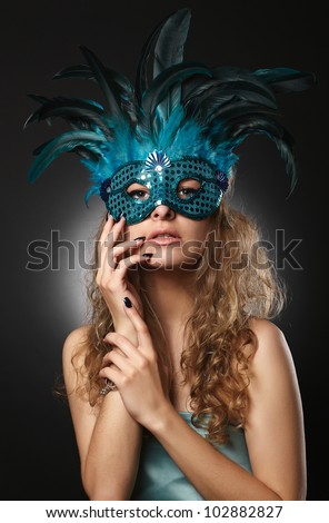 Beautiful young woman in carnival mask on a black background