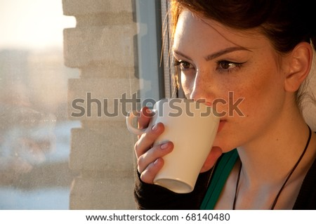 Beautiful young woman in casual wear dreaming with cup of hot coffee over window