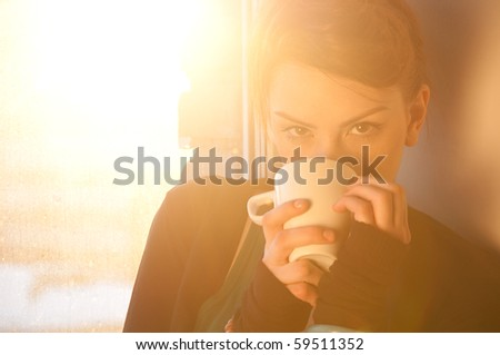 Beautiful young woman in casual wear dreaming with cup of hot coffee over window. Sun beam.