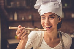 Beautiful young woman in chef hat is holding wooden spoon, looking at camera and smiling