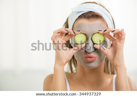 Beautiful young Woman in clay mud mask on face covering eyes with slices cucumber.  #344937329