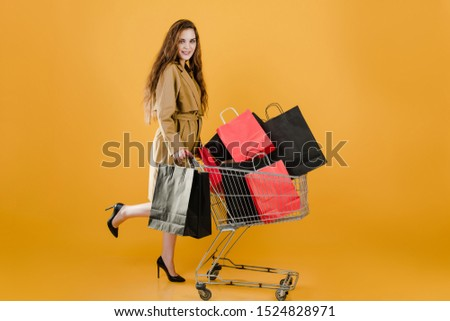 beautiful young woman in coat with shopping bags and pushcart isolated over yellow