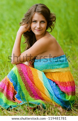Beautiful young woman in colorful dress sitting on grass, against green of summer park.