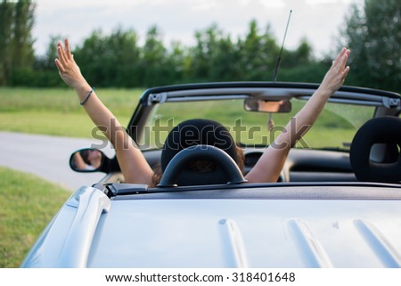 Beautiful young woman in convertible with hands up. Coupe convertible is bright blue.Interior is black-blue color, with upholstery in the same color.Focus on the handle behind her head. #318401648