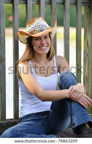 Beautiful young woman in country or western attire sitting on a dock in shade - cowboy hat and jeans - smiling