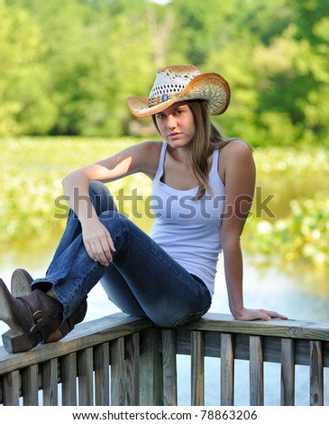 Beautiful young woman in country or western attire sitting on a dock railing with morning sunlight on her face - cowboy hat and jeans