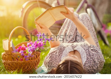 Beautiful young woman in dress laying on grass with basket of flowers and reading book near old vintage bicycle