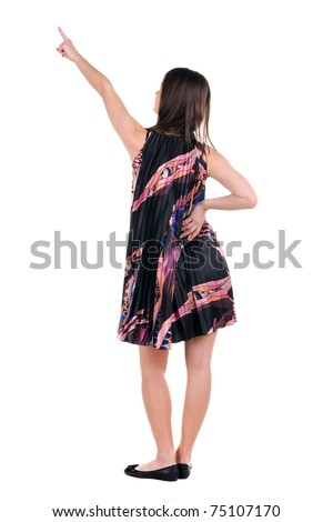 Beautiful young woman in dress pointing at wall. Rear view. Isolated over white.