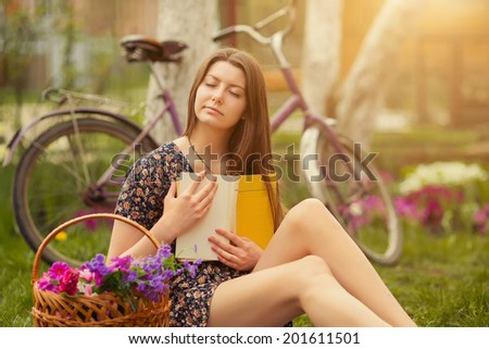 Beautiful young woman in dress sitting on grass with basket of flowers and reading book near old vintage bicycle