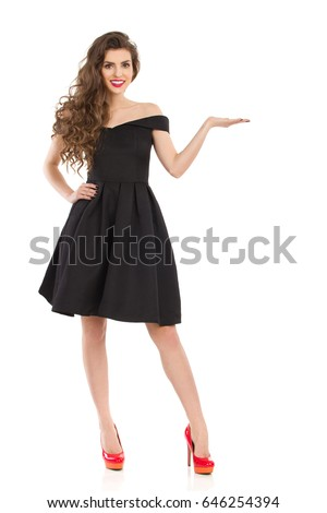 Beautiful young woman in elegant black cocktail dress and red high heels is standing with hand raised, presenting something and looking at camera. Front view. Full length studio shot on isolated.
