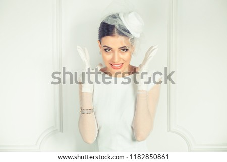 Beautiful young woman in elegant bridal outfit holding hands in air in stress while frowning looking at you camera with annoyed expression on white background. Retro vintage hair  clothing style bride