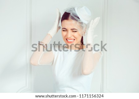 Beautiful young woman in elegant bridal outfit holding hands near temples in stress while frowning on white background