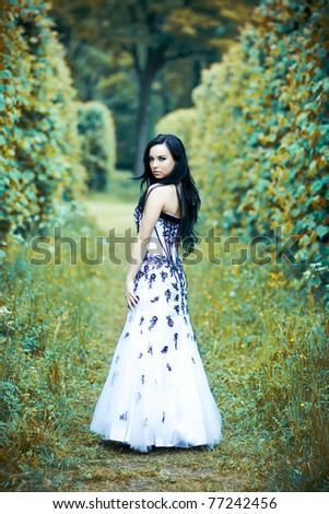 Beautiful young woman in elegant dress in dramatic magic park