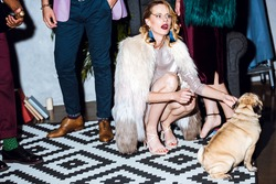 beautiful young woman in fur coat with pug puppy on party