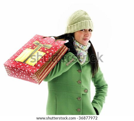 beautiful young woman in green coat and hat holding holiday bag over shoulder, clipping path
