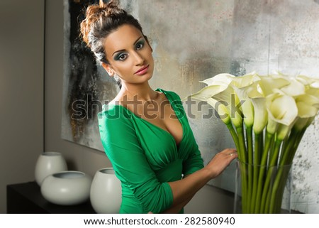 Beautiful young woman in green dress standing near vase with flowers