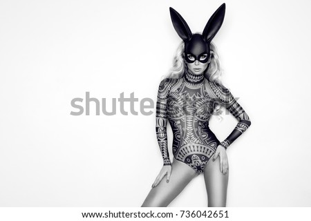 Beautiful young woman in Halloween, tattoo costume and black bunny  mask, standing on white background