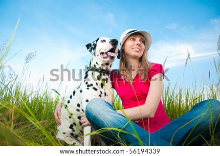 beautiful young woman in hat sitting in grass with her dalmatian dog pet and smiling. Blue sky in background and green grass in foreground.