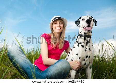 beautiful young woman in hat sitting in grass with her dalmatian dog pet and smiling. Both looking into the camera. Blue sky in background and green grass in foreground.