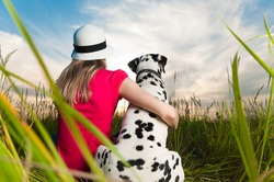 beautiful young woman in hat sitting in grass with her dalmatian dog pet with their backs to camera. Sunset cloudy sky in background and green grass in foreground.