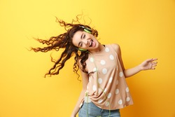 Beautiful young woman in headphones listening to music and dancing on yellow background