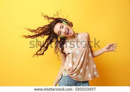 Beautiful young woman in headphones listening to music and dancing on yellow background #585033697