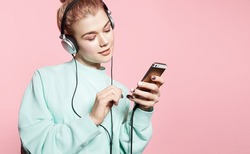 Beautiful young woman in headphones listening to music smiling with closed eyes standing on a pink background in a blue sweatshirt