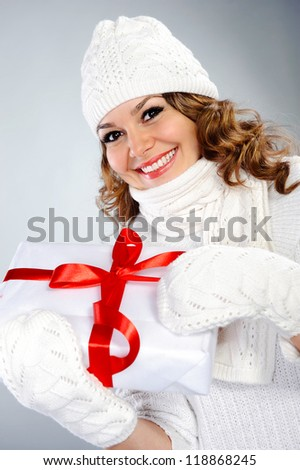 Beautiful young woman in knitted white clothes holding present box with red ribbon