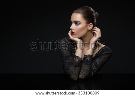 Stock Photo Beautiful young woman in lace top with red lips touching face. Over black background. Copy space.