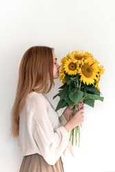 Beautiful young woman in linen dress holding sunflowers bouquet on white background. Autumn concept.