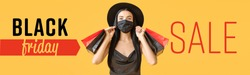 Beautiful young woman in medical mask and with shopping bags on color background. Black Friday sale