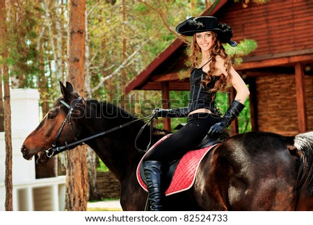 Beautiful young woman in medieval costume is riding on horseback.