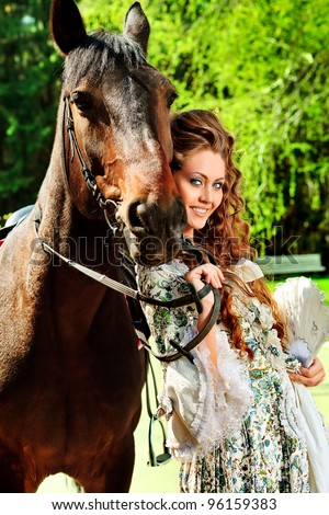 Beautiful young woman in medieval dress with a horse outdoor.
