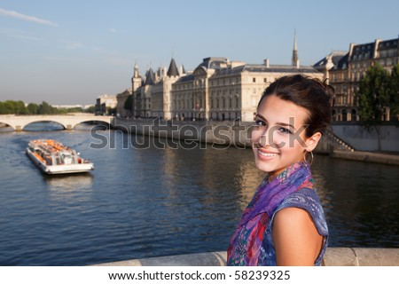Beautiful Young Woman in Paris on a bridge over the river Seine.
