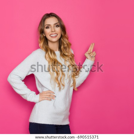 cd0ef6dd4 Beautiful young woman in pastel blue sweater is pointing , looking at camera  and smiling.